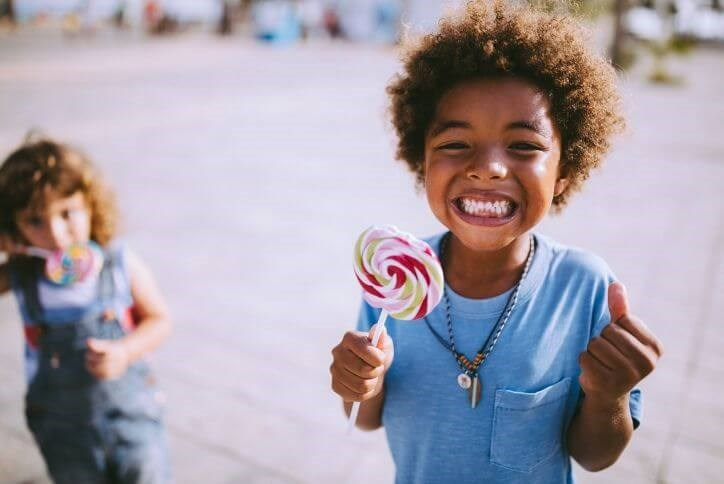 Excited boy with lollipop | Canyon Falls, a new home community in Northlake, Flower Mound and Argyle, TX.